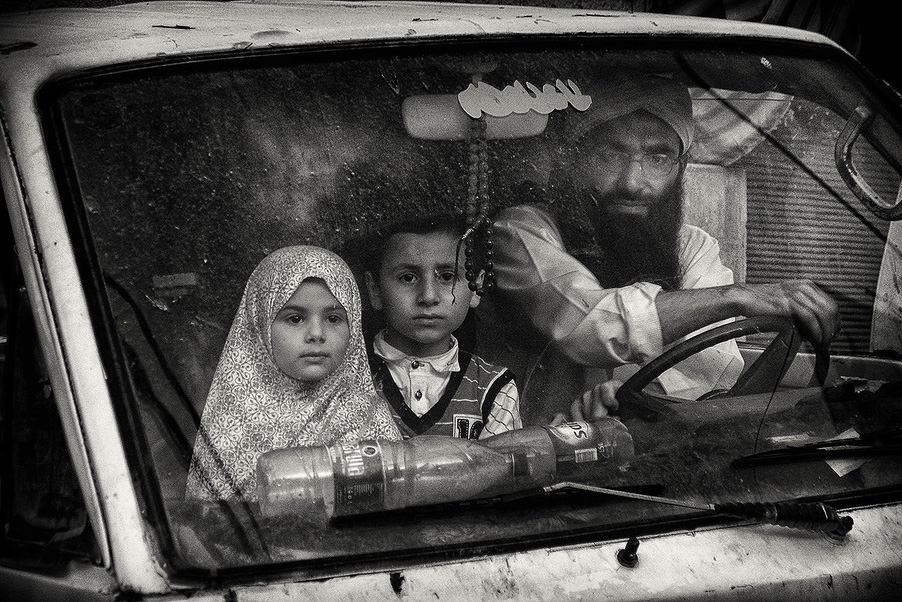 A car with this beautiful Serene family turning left and passing me by at a small intersection in Jordan. The briefest of encounters, forever etched in my mind's eye, © Marinka MASSËUS, Netherlands, Finalist Category A: Defining Family, Kuala Lumpur International Photoawards 2017 Winner