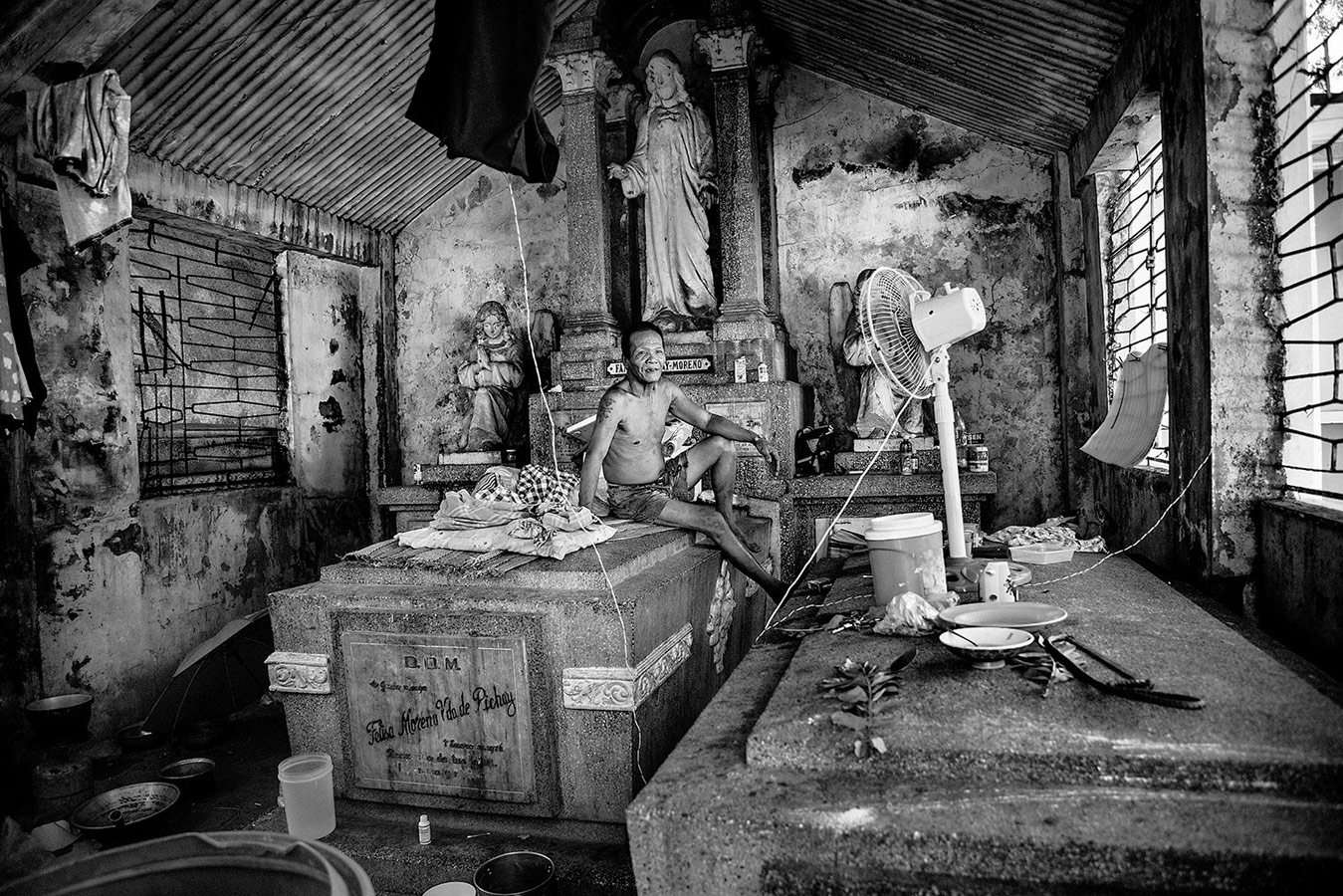 Ruben, 62, sit on top of his bed in one pantheon inside the northern cemetery of Manila, where he lives 30 years ago. © Bruno Gallardo, Spain, Kuala Lumpur International Photoawards - KLPA
